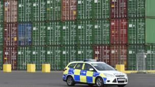 貨輪卸下大量集裝箱。若論體積,旁邊的警車根本不能與之相比。