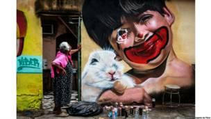 """Senhora observa grafite feito no muro de sua casa na Vila Operária, em Duque de Caxias, durante o evento """"Meeting of favela"""". Rio de Janeiro, 2013. Paulo Barros"""