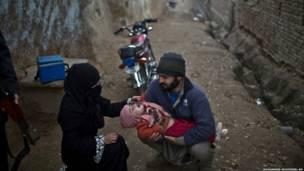 पाकिस्तान में एक आंतरिक विस्थापित आदमी अपने बच्चे को  पोलियो की दवा पिलवाते हुए. इसी हफ़्ते की शुरुवात में स्वास्थ्य कर्मियों के साथ चल रहा एक पुलिस वाला हमलावरों की गोली का निशाना बन गया था. पाकिस्तान दुनिया के उन तीन मुल्कों में से एक है जहाँ पोलियो एक बड़ी बीमारी है.