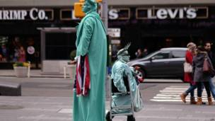 न्यूयॉर्क में स्टेच्यू ऑफ़ लिबर्टी का सा भेष बनाए हुए लोग