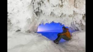 Иан Плант сидит в ледяной пещере