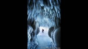 Сосульки свисают со сводов пещеры, в которую входит Иан Плант