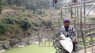 Житель деревни Горди Бахадур Чепанг с урожаем перебирается через реку