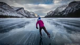 Uma pessoa patina em lago congelado no Canadá. (Foto: Paul Zizka, Cater News)