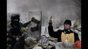 जेरोमे सेज़ीनी की कीएफ़ में एक पादरी और विरोधी प्रदर्शनकारी की तस्वीर