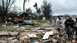 سكان محليون يمرون عبر ركام الأبنية في بورت فيلا، بعد أن ضرب إعصار بام الأرخبيل الواقع في جنوب المحيط الهادي، يوم الأحد، 15 مارس/آذار 2015