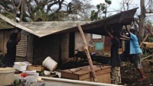 صورة تسلمتها وكالة فرانس برس يوم 15 مارس/آذار 2015 من الصليب الأحمر الأسترالي وتظهر مواطنين وهم يقومون بإزالة الحطام والتعامل مع الأضرار التي لحقت بمنازلهم في بورت فيلا