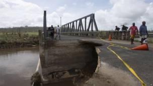صورة التقطت يوم 15 مارس/آذار 2015 من جانب اليونسيف باسيفك وتظهر أناس يسيرون على جسر تعرض للدمار نتيجة إعصار بام بالقرب من بورت فيلا في فانواتو. أسوشيتد برس