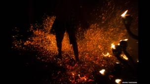The legs of a man performing a ritual in the dark using flames, Bali, Indonesia © Uruma Takezawa