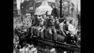 Фургон с пивом проезжает по Пикадилли-серкус 8 мая 1945 года. На заднем плане видны знаменитая статуя Эроса, которая во время войны была загорожена рекламными щитами.