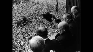 Британский премьер-министр Уинстон Черчилль (1874-1965) приветствует толпу, собравшуюся на улице Уайтхолл 8 мая 1945 г.
