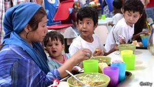 Inmigrantes comen en un albergue de Cáritas