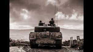 Soldiers sit in a tank on a hill in Lulworth firing range during training