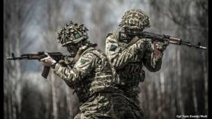 Two camouflaged soldiers stand back to back , holding guns, during Ukrainian military training