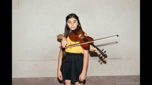 صورة لفتاة وخلفها ذراعان يمسكان آلة الكمان الموسيقية