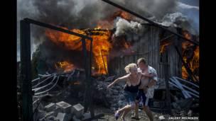 مدنيون يهربون من حريق في منزل، دمرته غارة جوية.