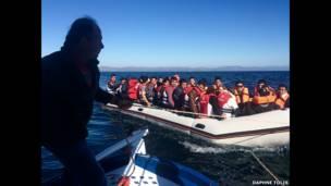 Рыбак тащит на буксире лодку с мигрантами
