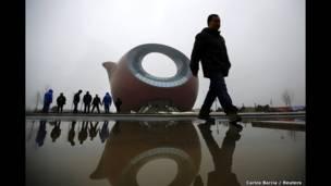 عمال يقفون إلى جوار بناية على شكل إبريق شاي في منطقة ووتشي