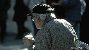 Persona mayor caminando en la calle con una bebida en la mano