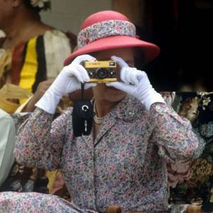 aking photographs with her gold Rollei camera