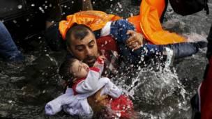 Un refugiado sirio sujeta a su hijo mientras lucha por salir de su bote en la isla griega de Lesbos.