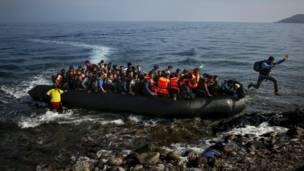 Un inmigrante afgano salta a tierra desde un bote sobrecargado de pasajeros al llegar a la isla de Lesbos.