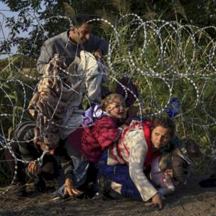 Inmigrantes sirios cruzan por debajo de una alambrada para entrar en Hungría a través de la frontera con Serbia. REUTERS/Bernadett Szabo
