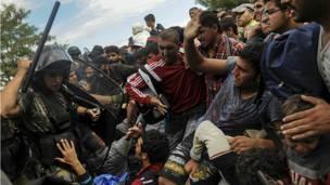 Un policía de Macedonia levanta su bastón en señal de amenaza hacia un grupo de inmigrantes que intentan entrar al país procedentes de Grecia. REUTERS/Alexandros Avramidis