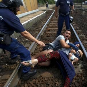 Policías húngaros intentan atrapar a una familia de inmigrantes que se lanzó a las vías del tren para evitar ser detenidos en la estación ferroviaria de la localidad de Bicske. REUTERS/Laszlo Balogh