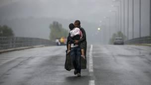 Un refugiado sirio besa a su hija mientras camina durante una tormenta hacia la frontera de Grecia con Macedonia. REUTERS/Yannis Behrakis