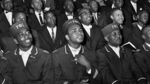 Alí escucha un discurso de Elijah Muhammad, líder de los musulmanes negros.