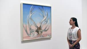A women looks at From the Faraway, Nearby, 1937, by Georgia O'Keeffe