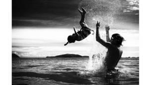 أب يلاعب ابنته في شاطئ البحر بتايلاند