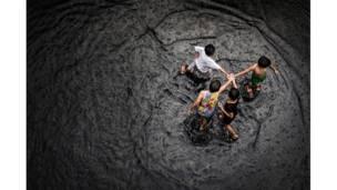 أطفال يلعبون بمياه الفيضانات