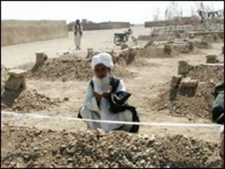 یک افغان در حال دعا برسر قبر قربانیان (آرشیو)
