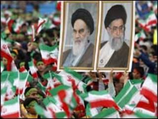 Estudantes seguram retratos de Khomeini (esq.) e Khamenei durante comemoração de aniversário da revolução islâmica (AP)