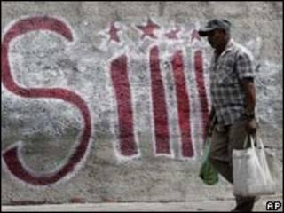 """Homem passa por muro grafitado com campanha pelo """"sim"""", em Caracas (AP)"""
