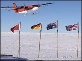 avião sobrevoando gelo perto de bandeiras de países envolvidos na missão