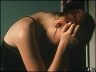 Una mujer se toma la cabeza en la cama