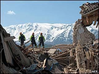 Bombeiros em casa destruída em Áquila