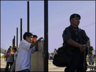 Crianças observam policial que guarda obras de muro na Argentina (AP, 8/4)