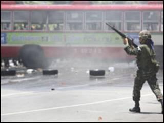 Policial aponta arma para cima em Bangcoc