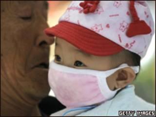 Bebê com máscara respiratória em Pequim