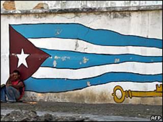 Un trabajador cubano cerca de un mural pintado en una pared de La Habana