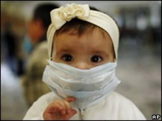 Menina de sete meses de idade usa máscara no aeroporto de Tijuana, no México