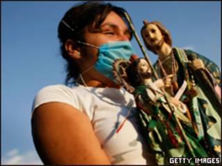 Mexicana com máscara para evitar contágio segura imagens religiosas (Getty Images, 28/4)