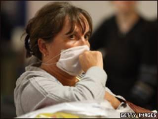 Mulher usa máscara cirúrgica após desembarcar no aeroporto de Gatwick, em Londres (Getty Images, 30/4)