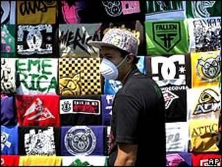 Mexicano com máscara passa por camisetas à venda na Cidade do México