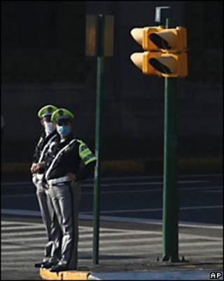 Dos policias con cubrebocas vigilan una de las calles en la Ciudad de México