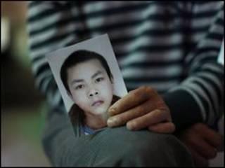 Một người Trung Quốc cầm ảnh người con trai 15 tuổi đã bị chết trong vụ động đất tại Tứ Xuyên